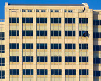 Two window washers near the top. Of a tall building in downtown Austin Texas Royalty Free Stock Photography