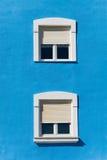 Two windows. On blue facade Stock Photography