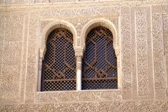 Two windows in an ancient Moorish castle. Two arched windows. The castle in the Spanish city of Granada. Fragment of the wall with Arabic script. Stone carving Royalty Free Stock Images