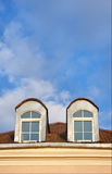 Two windows in attic. And blue sky at sunny day Stock Photos