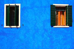 Two windows on blue house in burano island Stock Photos