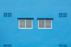 Two windows on the blue wall. Royalty Free Stock Photography