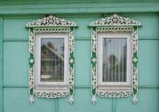 Two windows with carved platbands Royalty Free Stock Images
