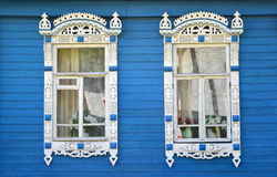 Two windows with carved platbands on the blue wooden house Royalty Free Stock Image