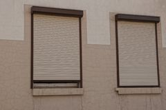 Free Two Windows Closed By Roller Shutters On A Brown Wall Royalty Free Stock Photography - 136439487