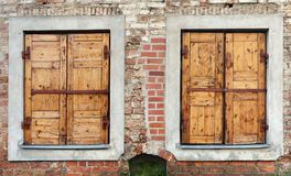Two windows with closed locked wooden blings in the aged bric. K wall of a ruined house. Panoramic collage from several outdoor street photos royalty free stock photography