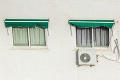 Two windows closed with roller shutters and air conditioning system installed on a hot summer day in Spain. Isolated on white wall royalty free stock photo