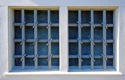 Two windows closed by wrought iron grates Royalty Free Stock Image