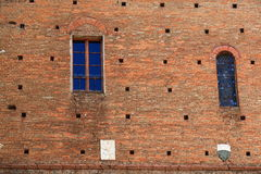 Two windows and coat of arms on an ancient wall Royalty Free Stock Images
