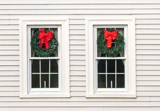 Two windows decorated with Christmas wreaths. Two Christmas wreaths hang on the windows of a white house royalty free stock images