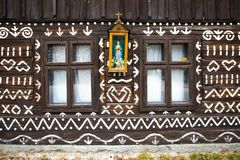 Two windows and decorations in village Cicmany. Cicmany, Slovakia - august 02, 2015: Old wooden houses in Slovakia village Cicmany, traditional painted with Royalty Free Stock Photos