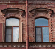 Two windows and drainpipe, on red brick wall Stock Photos