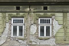 Two windows on the facade green dilapidated wall. Two windows on the facade green peeled dilapidated wall Stock Images