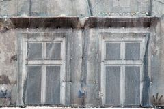Two windows on the facade of the old house closed mesh for repair stock photos