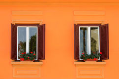 Two windows with flowers on wall Stock Images