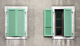Two windows, green shutters. Two windows with green shutters, one of them is half open royalty free stock image