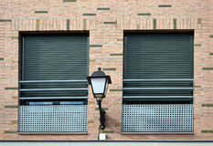 Two windows and lamppost. Two windows with green blinds and lamppost in the middle royalty free stock images
