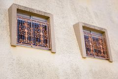 Two Windows with metal bars on the facade of the house close-up royalty free stock photos