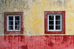 Two windows on an old and dirty wall of colorful house facade. Monte Funchal on Madeira island royalty free stock photos