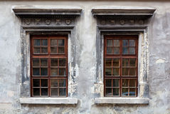 Two windows on an old gray stucco Stock Photo