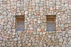Two windows in the old stone wall Stock Photo