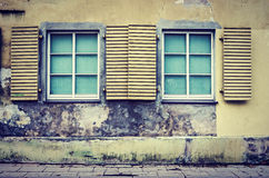 Two windows on old wall. Exterior of an old wall building with wooden shutters two windows stock photo