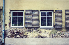Two windows on old wall with gotter. Exterior of an old wall building with wooden shutters two windows royalty free stock photo