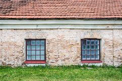 Two windows on old wall with lawn and roof Royalty Free Stock Images