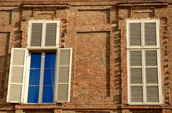 Two windows, one with a blue curtain Royalty Free Stock Image
