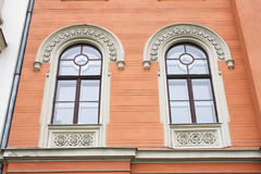 Two windows. On orange wall background house fasade Stock Photos