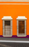 Two windows on orange wall Royalty Free Stock Photo