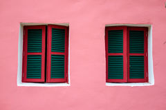 Two windows on pink wall. Lively style of architecture building Stock Photography