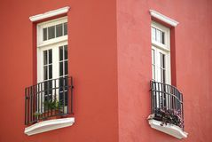 Two windows in red buiding. Architecture detail: Old worn white windows a red stucco building. Corner of the building. Located in San Juan, Puerto Rico Stock Images