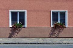Two windows with red flowers in the sun. royalty free stock photo
