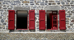 Two windows with red shutters. Grey stone house with two windows with red shutters Stock Photo
