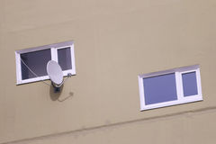 Two windows of residential building and white satellite dish Stock Photo