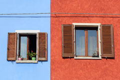 Two windows with shutters on colorful wall Stock Photo