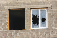Two windows in an unfinished house - one without a frame and glass, the other broken glass Stock Photo