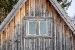 Two windows on a weathered and aged log cabin. Front view of two windows on a weathered and aged log cabin stock photo
