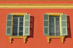 Two windows with window shades open on a red wall Stock Images