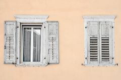 Two windows with window shutters in a beige house.  Stock Photography