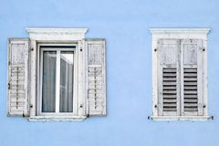 Two windows with window shutters in a blue house.  Stock Photography
