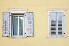 Two windows with window shutters in a yellow house.  Stock Photography