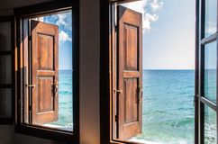 Two windows with wooden brown shutters opens amazing view on aquamarine endless sea and blue sky, no people around royalty free stock photography