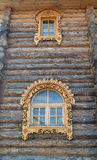 Two windows with wooden carved platbands on a timbered wall Royalty Free Stock Photography