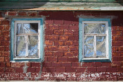 Two windows in wooden frame in red brick wall Stock Photos