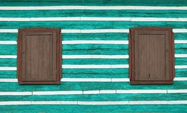 Two windows with wooden window shutters Royalty Free Stock Images