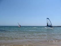 Two windsurfers with a blue and red sail in the sea. Water entertainment for sports people at sea or in the ocean Stock Images