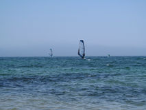 Two windsurfers are located symmetrically on the sea surface. Blue-turquoise sea, clear blue sky without clouds and two surfers are doing sports Royalty Free Stock Image