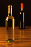Two wine bottles on wooden table and black background Stock Image
